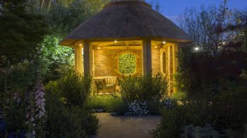 Wooden chair in thatched summerhouse lit at night