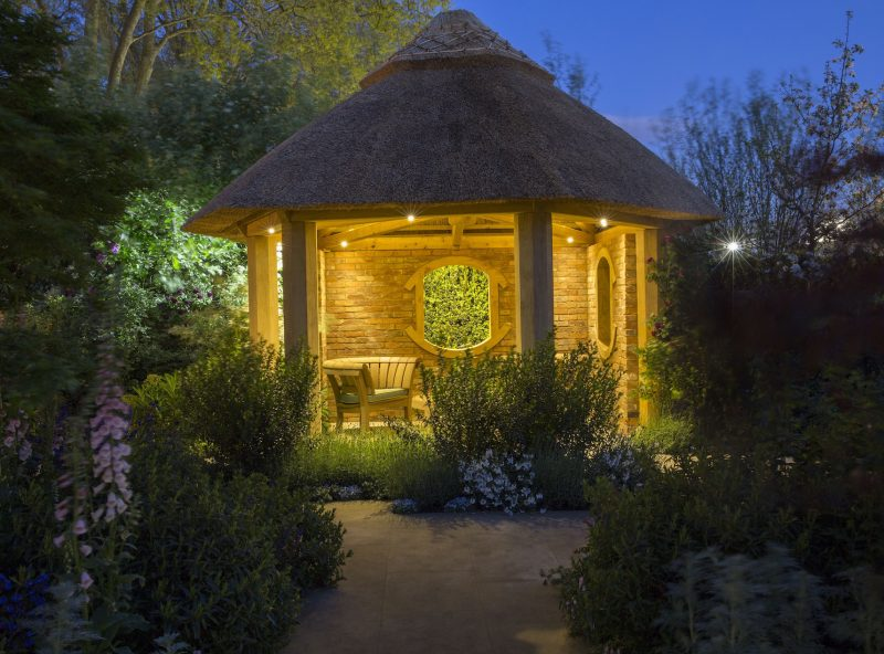 Oak summerhouse lit at night with Hunza garden lights - garden lighting installation and Oak frame building by Platts Horticulture